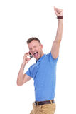 De toevallige jonge mens juicht terwijl op de telefoon toe Royalty-vrije Stock Afbeeldingen