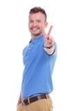 De toevallige jonge mens toont vredesteken Royalty-vrije Stock Fotografie