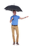 De toevallige jonge mens voelt de regen met een hand Royalty-vrije Stock Fotografie