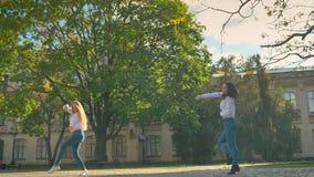 De toevallige Leuke Dansende Meisjes op het Vierkant in Openbare ruimte die Bewegingen tonen en presteren gelukkig, Gebouwen op A stock footage