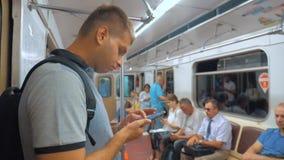 De toevallige lezing van de reizigersmens van het mobiele scherm van telefoonsmartphone terwijl blikken de navigator die op metro stock videobeelden