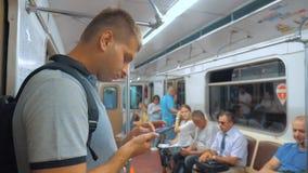 De toevallige lezing van de reizigersmens van het mobiele scherm van telefoonsmartphone terwijl blikken de navigator die op metro stock footage