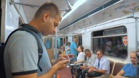 De toevallige lezing van de reizigersmens van het mobiele scherm van telefoonsmartphone terwijl blikken de navigator die op metro stock video