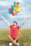 De toevallige mens houdt ballons met open wapens Royalty-vrije Stock Foto
