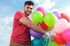De toevallige mens houdt heel wat baloons Stock Fotografie