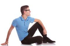 De toevallige mens legt op de grond en kijkt weg stock fotografie