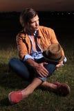 De toevallige mens met hoed op knie kijkt weg Royalty-vrije Stock Foto's