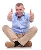 De toevallige midden oude mens zit en toont duimen Royalty-vrije Stock Foto's