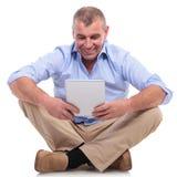 De toevallige oude mens zit en bekijkt tablet Royalty-vrije Stock Foto