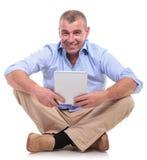 De toevallige oude mens zit en houdt tablet Royalty-vrije Stock Fotografie