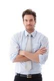 De toevallige zakenman status bewapent het gekruiste glimlachen Stock Foto