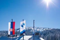 De toevluchtvlaggen van Serviër en van de ski op sneeuwbergachtergrond en zon Royalty-vrije Stock Afbeeldingen