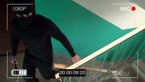 De toezichtcamera ving de rover in een masker met een koevoet stock video