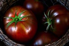 De tomaten in een mand sluiten omhoog stock afbeelding