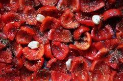De tomaten liggen op een bakselblad, klaar te bakken In de zon gedroogde tomaten met knoflook De achtergrond van het voedsel Royalty-vrije Stock Afbeelding