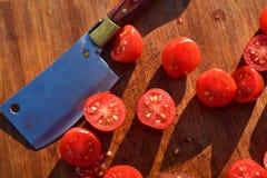 De tomaten van de besnoeiingsdruif op houten scherpe raad Stock Afbeelding
