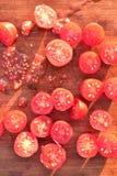 De tomaten van de besnoeiingsdruif op houten scherpe raad Stock Afbeeldingen