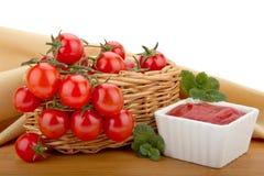 De tomaten van de kers in een mand en een tomatenpuree Stock Afbeelding
