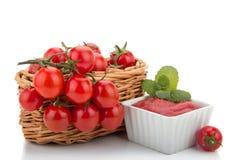 De tomaten van de kers in een mand en een tomatenpuree Stock Foto