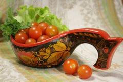 De tomaten van de kers met peterselie in Hohloma stock foto's