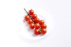 De tomaten van de kers op een witte plaat Stock Afbeeldingen