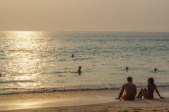 De toneel mooie romantische zonsondergang over het overzees met mensen silhouetteert in status in water en geniet van de avondsin Royalty-vrije Stock Foto's