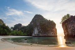 De toneelkromme van tropisch strand in ochtendlicht, zonsopgang glanst door fantastische klip op blauwe overzees en wit zandstran royalty-vrije stock afbeeldingen