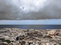De toneelmening van een kustlijn met rotspools op de rand van een kalksteenstrand met heldere blauwe kalme de zomer overzeese dar stock afbeeldingen