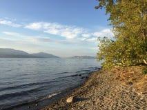 De toneelmening van het meerlandschap met rotsachtig strand en golven op oever stock foto's