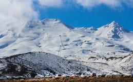 De toneelsneeuw behandelde bergpiek met mist die zich in de mooie duidelijke blauwe die hemel bewegen waar lijn van auto's op een royalty-vrije stock afbeelding