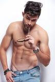 De topless jonge mens bijt zijn zonnebril Royalty-vrije Stock Afbeeldingen