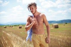 De topless mens openlucht met stro in mond kijkt weg Royalty-vrije Stock Foto's