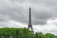 De Toren die van Eiffel over bomen met stormachtige wolken te voorschijn komen Royalty-vrije Stock Fotografie