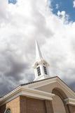 De Toren van de kerktorenspits onder Onheilspellende Stormachtige Onweersbuiwolken Royalty-vrije Stock Foto's