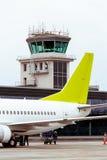De toren van de luchtcontrole bij luchthaven, met vliegtuigstaart op voorgrond Royalty-vrije Stock Afbeeldingen
