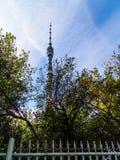 De toren van de Ostankinotelevisie - achter de bomen en de omheining Royalty-vrije Stock Afbeelding