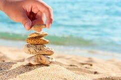 De toren van de steen op zand met hand. Royalty-vrije Stock Afbeelding