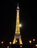 De toren van Eiffel bij nacht met erachter maan Stock Afbeeldingen