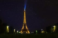De Toren van Eiffel bij nacht wordt verlicht die stock afbeeldingen