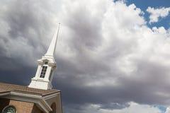 De Toren van de kerktorenspits onder Onheilspellende Stormachtige Onweersbuiwolken Stock Afbeelding