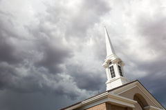 De Toren van de kerktorenspits onder Onheilspellende Stormachtige Onweersbuiwolken Stock Fotografie