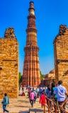 De toren van Qutbminar die door de geruïneerde Quwwat-ul-islammoskee in Qutub complexe Minar wordt gezien - New Delhi, India royalty-vrije stock foto