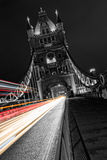 De torenbrug in Londen in zwart-wit, het UK bij nacht met onduidelijk beeld kleurde autolichten Stock Foto's