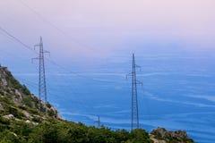 De torens van de hoogspanningselektriciteit op groene berg dichtbij overzees Stock Foto's