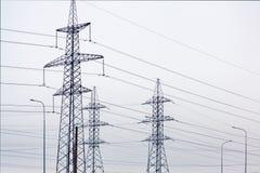 De torens van de machtslijn met draden tegen een bewolkte hemel stock afbeelding