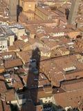 De torenschaduw van Asinelli over rode de baksteendaken van Bologna Stock Afbeeldingen