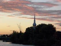 De torenspits van de kerk bij zonsondergang Stock Foto