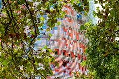 De Torre-Gloriën, die vroeger als Torre Agbar worden bekend die tussen de bomen in Barcelona, Spanje wordt gezien royalty-vrije stock afbeeldingen