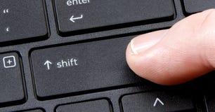 De touche 'majuscules' d'ordinateur avec le bouton de pressing de doigt Photographie stock