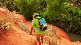 De touristes s'élève vers le bas entre les roches du Fée-courant à la fin de rivière banque de vidéos
